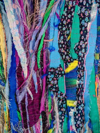 Colourful torn fabric strips, cords and wool, sewn together in a striped pattern. Textile art textured background. Vertical. Stock Photo