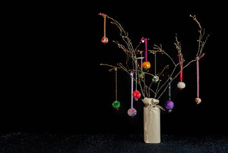 Christmas twig tree table decoration in rustic theme with colourful handmade hanging baubles. Black background and glittery base with copy space. Stock Photo - 129949495