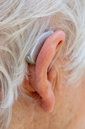 Hearing aid. Female pensioner with white hair wearing a Behind The Ear, BTE, hearing aid. Close up of ear and device viewed from behind.