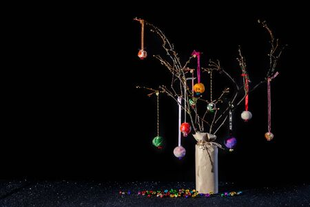 Christmas twig tree table decoration in rustic theme with colourful handmade hanging baubles. Black background and glittery base with jungle bells and copy space. 免版税图像