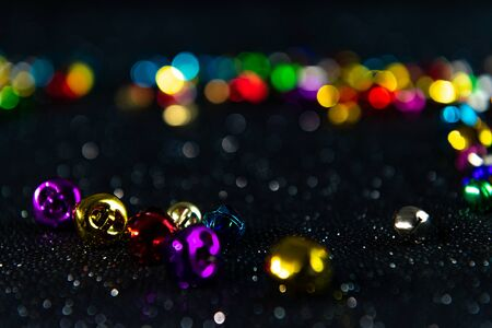 Multi-colored Christmas jingle bells. Black blurred bokeh glitter background. Shallow depth of field. For overlay, background or texture. 免版税图像