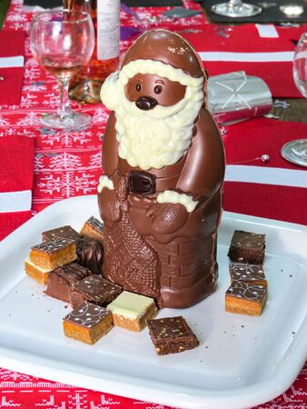 Chocolate Santa Claus with square chocolate treats on a red festive table on Christmas day.