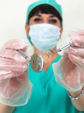 Blurred woman dentist. Focus on dental tools. Photographed from patient point of view. Wearing face mask, green hair net and uniform. Hands in latex gloves. Making eye contact. Plain pale background.