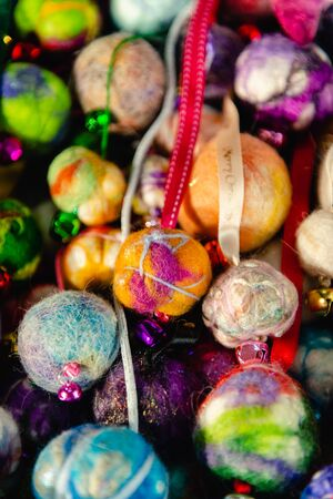 Colourful Christmas baubles. Handmade felted wool, ribbons and jingle bells. Vertical. 免版税图像