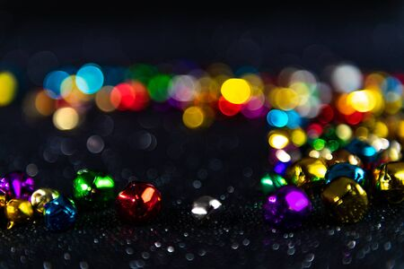 Colorful Christmas jingle bells. Black blurred bokeh glitter background. Shallow depth of field. For overlay, background or texture. 免版税图像