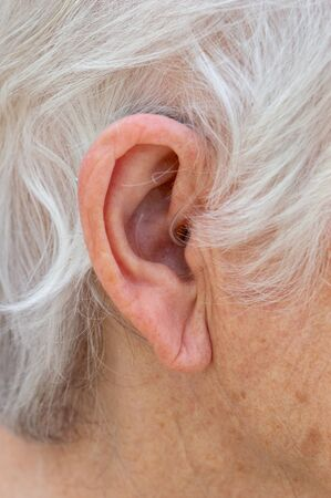Hearing aid. Female pensioner with white hair wearing a Behind The Ear, BTE, hearing aid. Close up of ear device almost invisible.