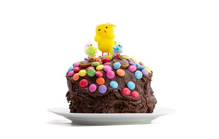 Easter cake on a white background. Fun kids chocolate cake decorated by a child with chocolate frosting covered in colorful chocolate beans and Easter chicks. Decoration sliding down sides of cake. 免版税图像