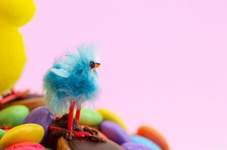 Easter cake chick and colorful chocolate bean decoration on a pink background. Close up of fun kids blue Easter chick. Copy space.