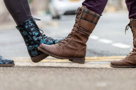 Foot tap. New novel greeting to avoid the spread of coronavirus. Two women friends meet in a British street. Instead of greeting with a hug or handshake, they touch their feet together instead.