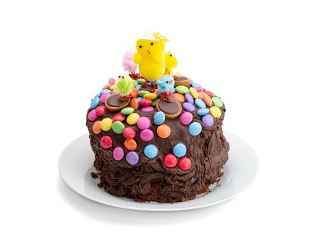 Easter cake on a white background. Fun kids chocolate cake decorated by a child with chocolate frosting covered in colorful chocolate beans and Easter chicks. Top and side view. 免版税图像