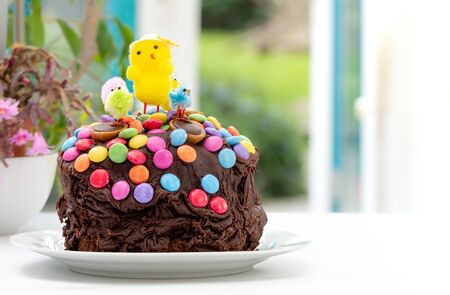 Fun kids chocolate Easter cake decorated by a child with chocolate frosting covered in colorful chocolate beans and Easter chicks. Decoration sliding down sides of cake. In front of garden window.