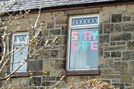 Wrexham, UK - March 24, 2020: Coronavirus lock down message in window. STAY SAFE made from coloured paper. A way to connect to the community with well wishes during isolation in the pandemic.