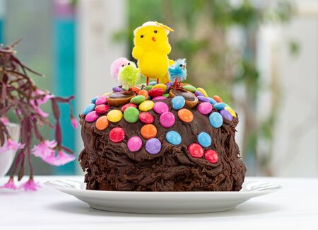 Fun kids chocolate Easter cake decorated by a child with chocolate frosting covered in colorful chocolate beans and Easter chicks. Decoration sliding down sides of cake. In front of kitchen window.