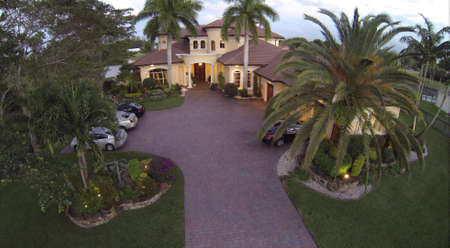 Beautiful home at dusk in South Florida with lots of palm trees   Imagens
