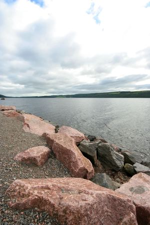loch ness from the shore with rocks Stock Photo