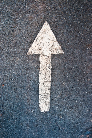 The White arrow on the road background Stock Photo - 8967636