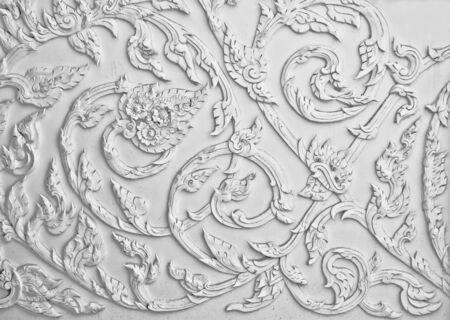 The White stucco design of native thai style on the Wall photo