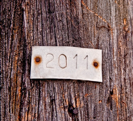 The Aluminum plate of 2011 on old wood background photo