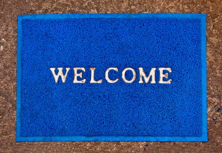 The Doormat of welcome text on floor background photo