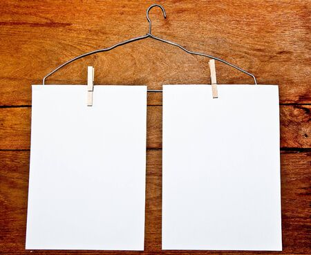 The White papers and hanger on wood background photo