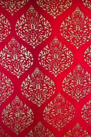The Traditional Thai style art golden painting pattern on red wall in temple. This is traditional and generic style in Thailand. No any trademark or restrict matter in this photo.