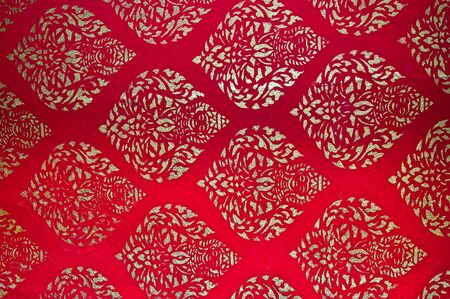 The Traditional Thai style art golden painting pattern on red wall in temple. This is traditional and generic style in Thailand. No any trademark or restrict matter in this photo. Stock Photo - 12617251