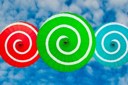 The Colorful of umbrella isolated on blue sky background photo