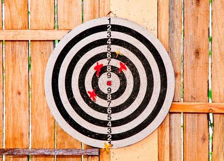 The Dartboard isolated on wood background photo