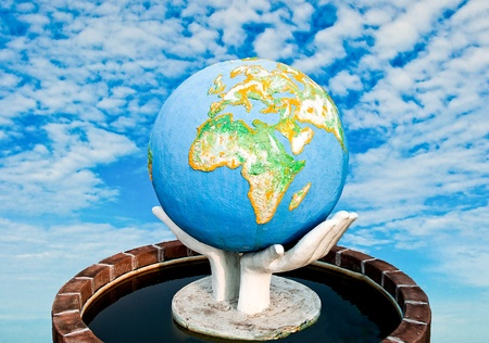 The Sculpture of world in hand on blue sky background photo