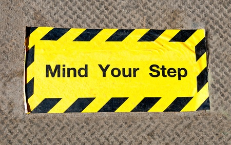 The Sign caution mind the step on steel floor photo