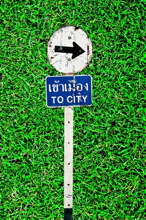 The Sign of  to city on green grass background photo