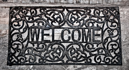 mat: The Doormat curved steel of welcome text on floor background Stock Photo