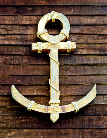 The Old wooden anchor on wood wall background