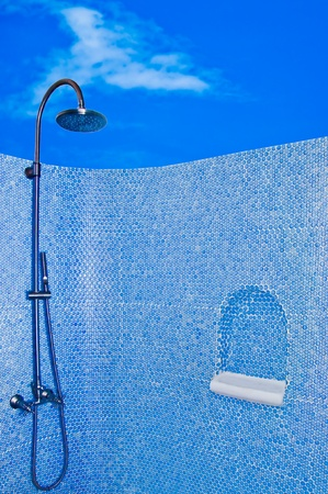 The Modern shower head in restroom isolated on blue sky background photo