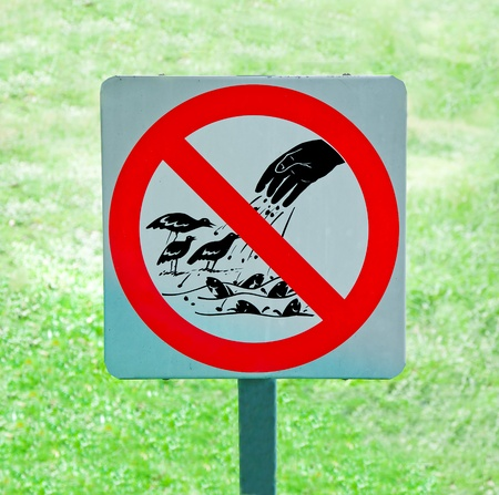 The sign of no feeding bird and fish on green grass background photo