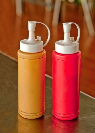 squirting ketchup: Mustard and ketchup bottle on dining table