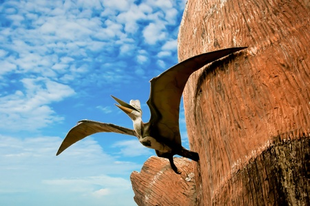 Sculpture of bird in dinosaur period on blue sky background photo