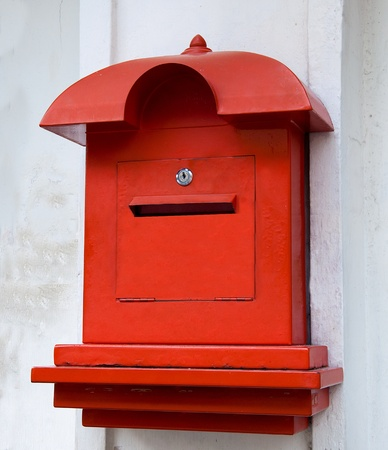 Red postbox  on white wall background photo