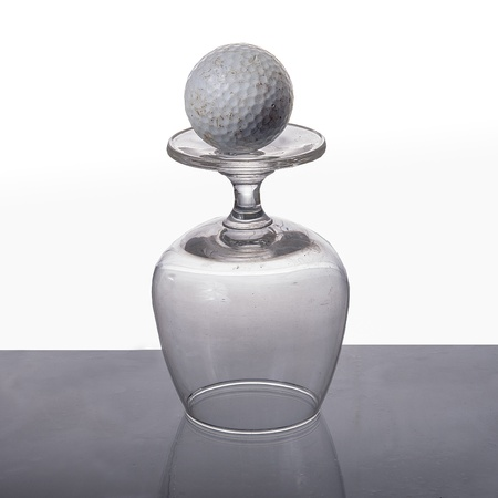 Empty wine glass with golf ball isolated on white background photo