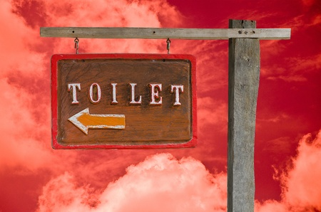 Wooden sign of toilet isolated on sky background photo