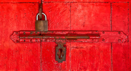 The Old master key and old bolt on red wooden door photo
