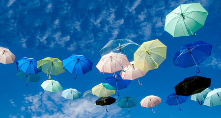 Multicolored umbrellas against blue sky background photo