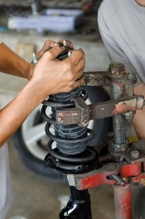 shock absorber: Auto car mechanic working on car shock absorber in car service workshop Stock Photo