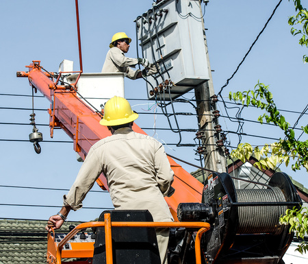 Minburi, Thailand- Nov 9:Electrician are installing high powered electric cables to cope with the increasing power usage of cities surrounding Bangkok.  in minburi Thailand on Nov 9,2013