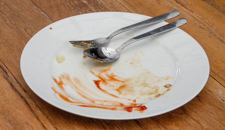 Dirty plate with spoon and fork on wood table Stock Photo