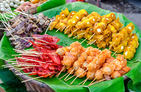stuffed fish: Snack thai style of Deep fried crispy dumpling Quail egg and fried shrimp ball  and grill dried squid and grill sweet fish on banana leaf background Stock Photo