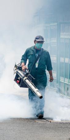 dengue: Laksi, Bangkok, Thailandia - 11 marzo L'ufficiale non identificato sta spruzzando chimico per un'epidemia di febbre dengue il 11 marzo 2014 in Laksi, Bangkok, Thailandia