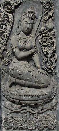 Deva sculpture on cement wall photo