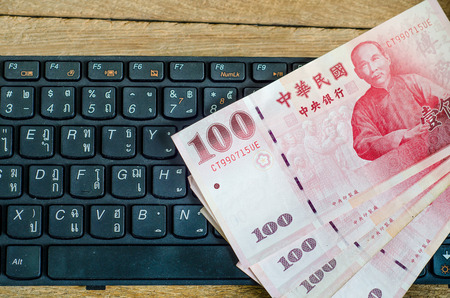 hundreds and thousands: 100 Taiwan Dollar bill on keyboard