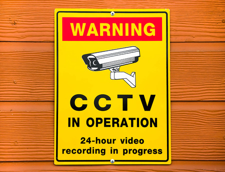 Video surveillance sign. CCTV Camera on wood background photo
